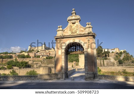 Alcantara Bridge across the river Tagus, leading to the historical city of Toledo, Spain, with the city walls and the Alcazar castle