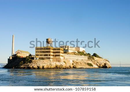 Alcatraz island in San Francisco Bay at sunset - stock photo