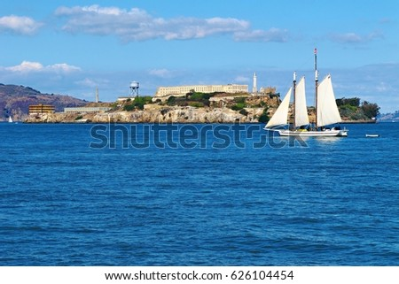 Alcatraz island, the legendary prison, view with sail ship in bay. Calm blue sea, sunny day with small clouds.