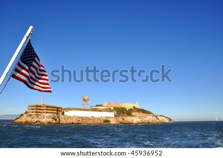 Alcatraz Island with the American Flag in the foreground. - stock photo
