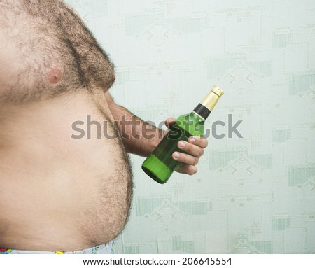 Alcohol abuse Color photo of a fat man with full luxury green glass bottle beer on textured green wall with wallpaper Empty copy space for inscription - stock photo