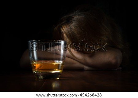 Alcohol addicted young woman with a glass of whisky