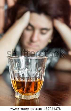 Alcohol addiction : Drunk and depressed hispanic woman (focused on her drink)