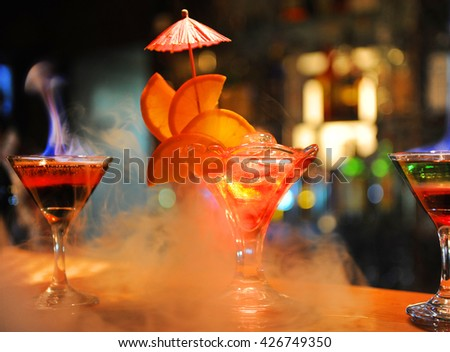 Alcohol bar, cocktail glass on bar counter, cocktail glass in a bar, Drinking cocktail in bar, cocktail in the glass with straws, burning cocktail, Hot drink, Fresh drink coctail on a color background