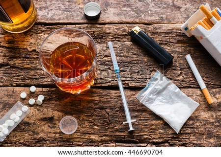 alcohol, cigarettes, drugs, pills on a wooden background
