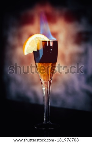 alcohol cocktail with alcohol and flame in wineglass, vintage stylized photo