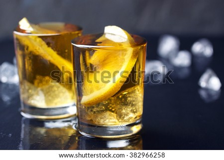Alcohol cocktail with brandy, whiskey, lemon and ice in small glasses with copy space