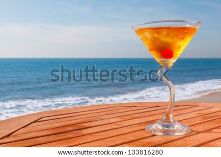 alcohol cocktail with cherry, ice on wooden table  background of sea and sky - stock photo