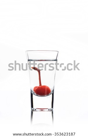 Alcohol cocktail with cherry in shot glass isolated on white background