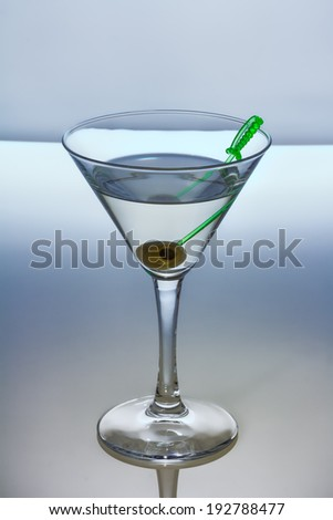Alcohol cocktail with dry martini and olive on skewer