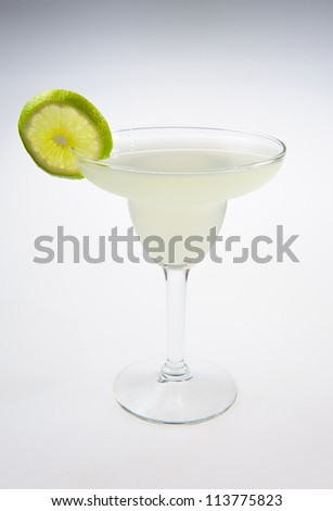 Alcohol cocktail with lime over white background