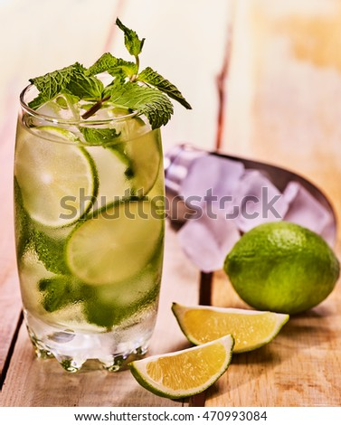 Alcohol drink. On wooden boards glass with alcohol drink and ice cubes. Drink two hundred eighty three cocktail mohito and quartered lime with mint leaf and ice cubes scoop. Light wooden background.