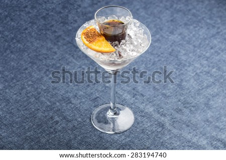 Alcohol shot in martini glass with orange and cinnamon on blue background - stock photo