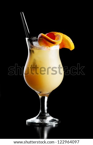 Alcohol yellow  drink in cocktail glass with piece of orange and red cherry