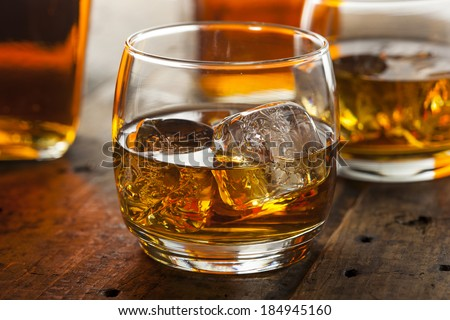 Alcoholic Amber Whiskey Bourbon in a Glass with Ice - stock photo