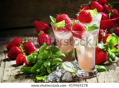 Alcoholic cocktail feeling with Cachaca, cranberry drink, strawberries, lime juice, green basil, and ice cubes, vintage wooden background, selective focus - stock photo