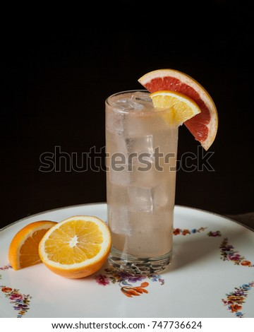 Alcoholic cocktail garnished with a slice of blood orange on dark rustic background