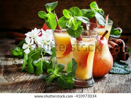 Alcoholic cocktail, Palma de Pear with pear vodka, cinnamon, mint, lime and apple juice and ice cubes, vintage wooden background, selective focus - stock photo