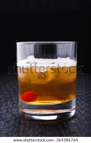 alcoholic cocktail with cherry on black background