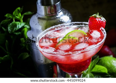 Alcoholic cocktail with strawberry, lime and ice, black background, selective focus
