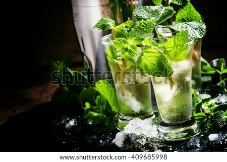 Alcoholic cocktail with vodka, mint tea, lemon juice, ice, sugar syrup and fresh peppermint, black background, selective focus - stock photo