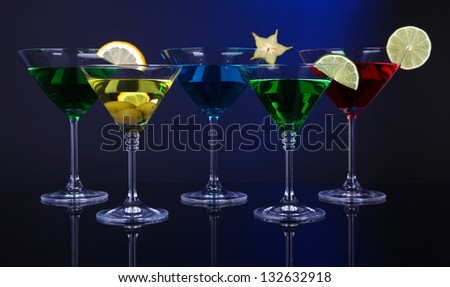 Alcoholic cocktails in martini glasses on dark blue background - stock photo