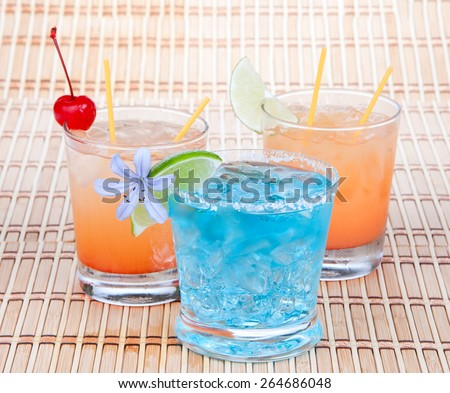Alcoholic Cocktails. Three drinks beverages Blue lagoon tropical Martini tequila sunrise margarita with cherry lime pineapple juice and flower  - stock photo