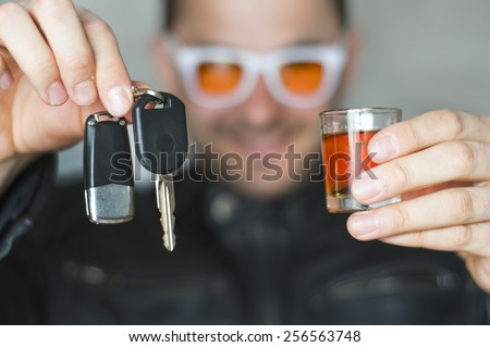 Alcoholic drink and car keys in hands - do not drink and drive concept - stock photo