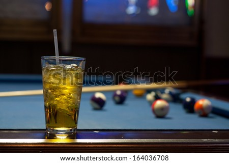 Alcoholic Drink On a Pool Table With Balls and Blue Neon Light - stock photo