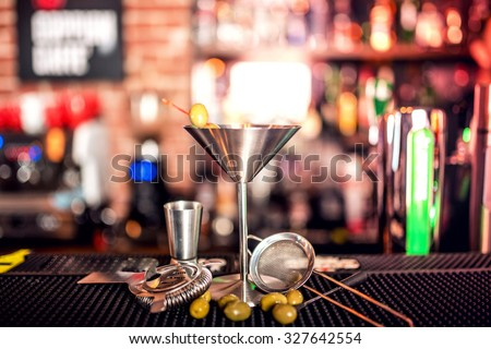 alcoholic drink on bar counter. Dry martini with ice and olives, served cold in restaurant, bar or pub. - stock photo