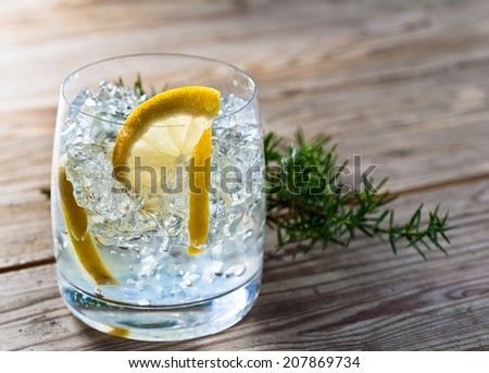 alcoholic drink with lemon and ice on a old wooden table - stock photo