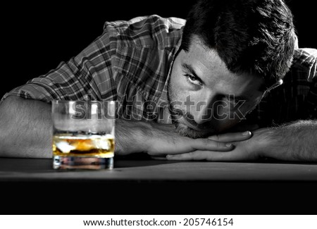 alcoholic drunk and wasted but attractive man sitting at table looking whiskey glass thinking in his alcohol addiction problem trying to avoid temptation and desire to drink in alcoholism concept  - stock photo