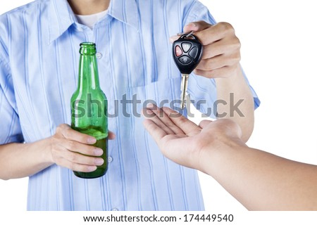 Alcoholic giving a car key to someone for driving the car - stock photo