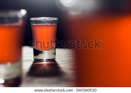 Alcoholic glasses with orange alcoholic drink are on the table. - stock photo