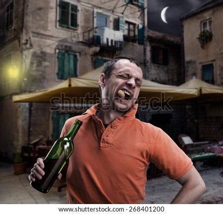 Alcoholic is opening a bottle of wine - stock photo