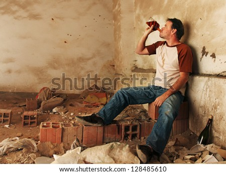 Alcoholic Man Drinking and Sitting against a filthy wall - stock photo