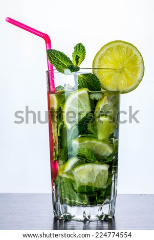 Alcoholic mojito cocktail on the table and white background - stock photo