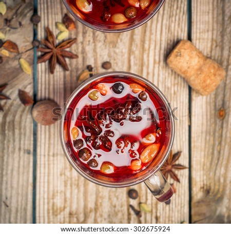 alcoholic mulled red wine with spices on a wooden table. toned image - stock photo