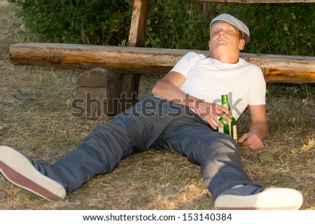 Alcoholic passed out on the ground in a park lying with his head cradled against a wooden bench holding his bottle of alcohol in his hand - stock photo