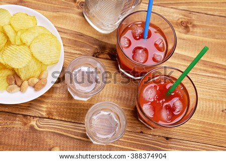 Alcoholic tomato cocktail with ice, bottle of vodka, stacks of vodka and snack of chips and nuts in pub or restaurant - stock photo