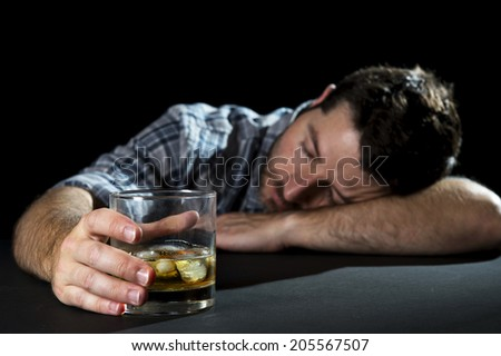 alcoholic wasted man sleeping drunk holding whiskey glass with head resting on table in alcohol addiction , drinking abuse and alcoholism concept isolated on black background