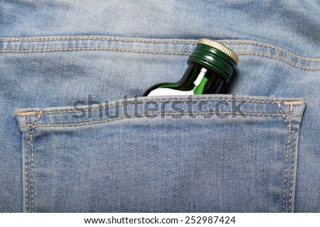 alcoholism concept - bottle with alcohol in back pocket of blue jeans - stock photo