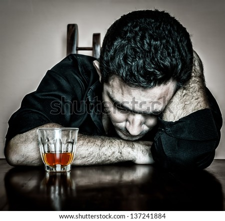 Alcoholism : Grunge bleached portrait of a lonely and desperate drunk hispanic man - stock photo