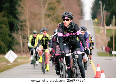 ALDERGROVE, BC/CANADA - MARCH 1, 2015: A cyclist leads the pack during the Escape Velocity Spring Series cycling race near Aldergrove, British Columbia on March 1, 2015.