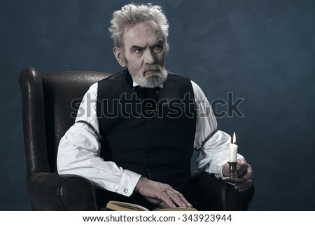 Alert Dickens Scrooge Man Sitting in Chair with Book Holding Candlestick. - stock photo