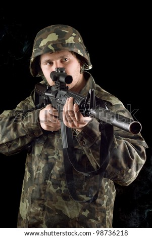 Alerted soldier keeping a gun in studio - stock photo
