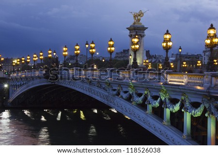 Alexander the Third bridge and Seine under shining lamps at night in Paris - stock photo