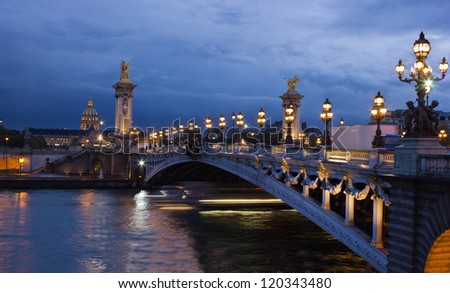 Alexander the Third bridge and Seine with golden Invalides dome and lights of cruise boat at night in Paris - stock photo
