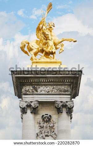 Alexandre III bridge golden statue in Paris, France  - stock photo