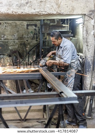 Alexandria, Egypt - March 25 ,2016: Man work with electric wheel grinding.